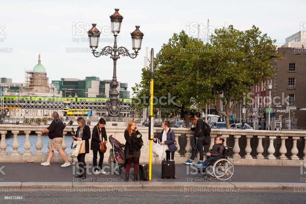 People at bus stop on O'Connell bridge stock photo