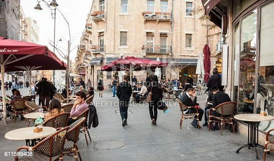 Jerusalem, Israel - February 19, 2014: People sitting in cafe terrace at Jaffa Road street in the evening. Jaffa Road is one of the longest and oldest major streets in Jerusalem.
