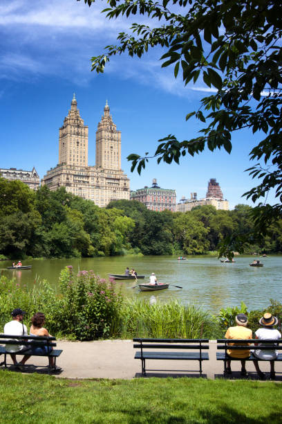 People at Central Park Lake and West Side cityscape skyline, Manhattan, NYC stock photo