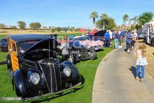 Palm Springs, California, United States - January 27th, 2019: People at charity car show admiring rows of classic, hot rod and special interest cars parked at a golf course in Palm Springs, California