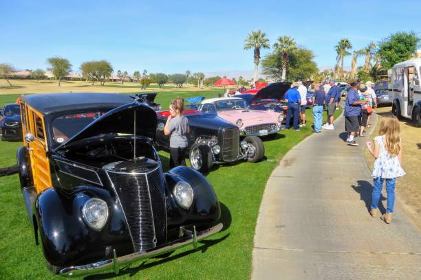 People at charity car show admiring rows of classic, hot rod and special interest cars parked at a golf course Palm Springs, California, United States - January 27th, 2019: People at charity car show admiring rows of classic, hot rod and special interest cars parked at a golf course in Palm Springs, California car show stock pictures, royalty-free photos & images