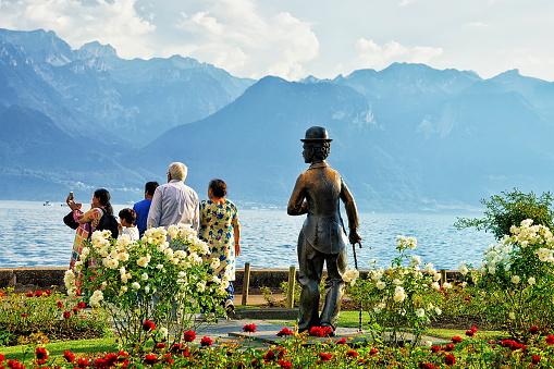 People at Charlie Chaplin statue at Geneva Lake of Vevey