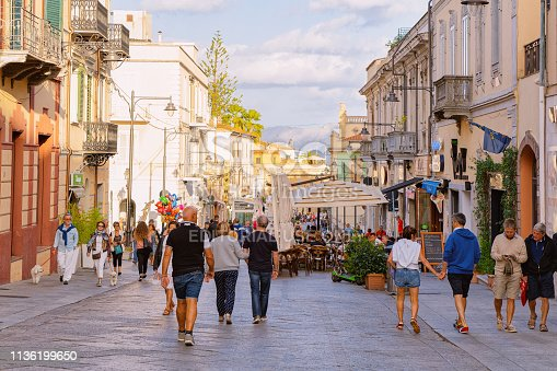 Olbia, Italy - September 11, 2017: People at Corso Umberto I Street in Old city of Olbia on Sardinia Island in Italy. Tourists and Town architecture on Italian Sardegna.