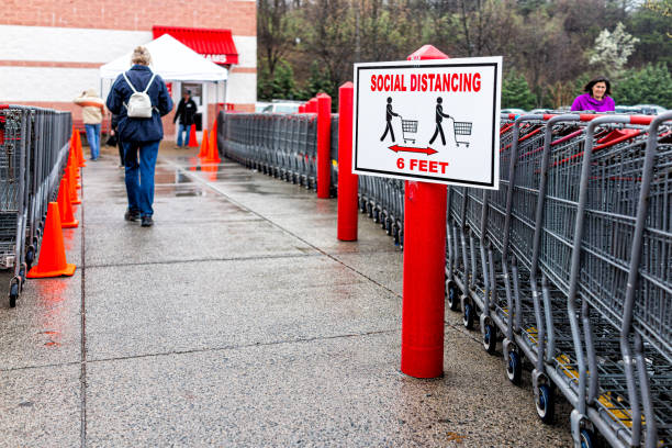 People at entrance to Costco membership club store during Coronavirus Covid-19 outbreak with sign for social distancing stock photo