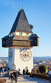 Graz, Austria - February 16, 2019: People at Grazer Uhturm Clock Tower on Schlossberg Castle hill on Street in Downtown and Old city of Graz in Austria. Town in Styria in Europe. Travel and history