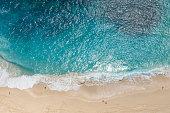 High angle view of sea, sand, and people at Kelingking Beach, Nusa Penida, Bali.