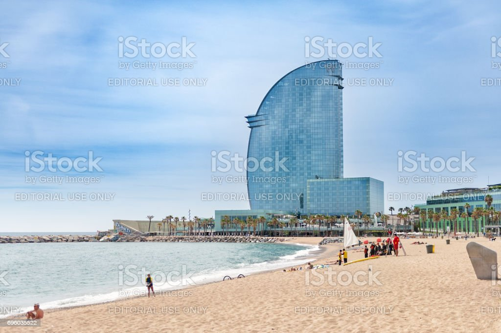 People at sandy Barceloneta beach with W hotel on a background stock photo