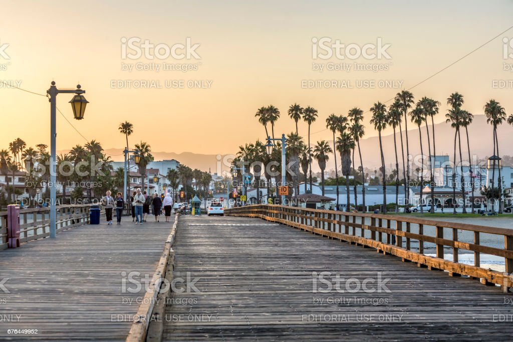 people at scenic old wooden pier in Santa Barbara in sunset Santa Barbara: people at scenic old wooden pier in Santa Barbara in sunset. The pier was completed in 1872 and was the longest pier at that time in the USA. Beach Stock Photo