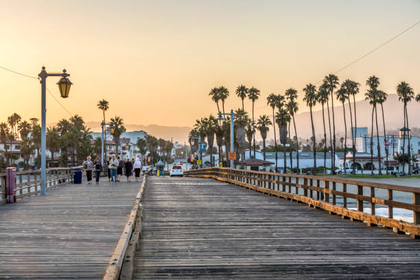 people at scenic old wooden pier in Santa Barbara in sunset Santa Barbara: people at scenic old wooden pier in Santa Barbara in sunset. The pier was completed in 1872 and was the longest pier at that time in the USA. santa barbara california stock pictures, royalty-free photos & images