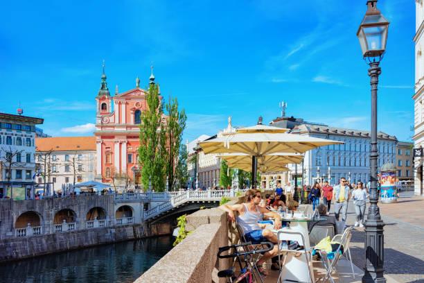 people at sidewalk cafe on triple bridge ljubljanica river ljubljana - slovenia foto e immagini stock