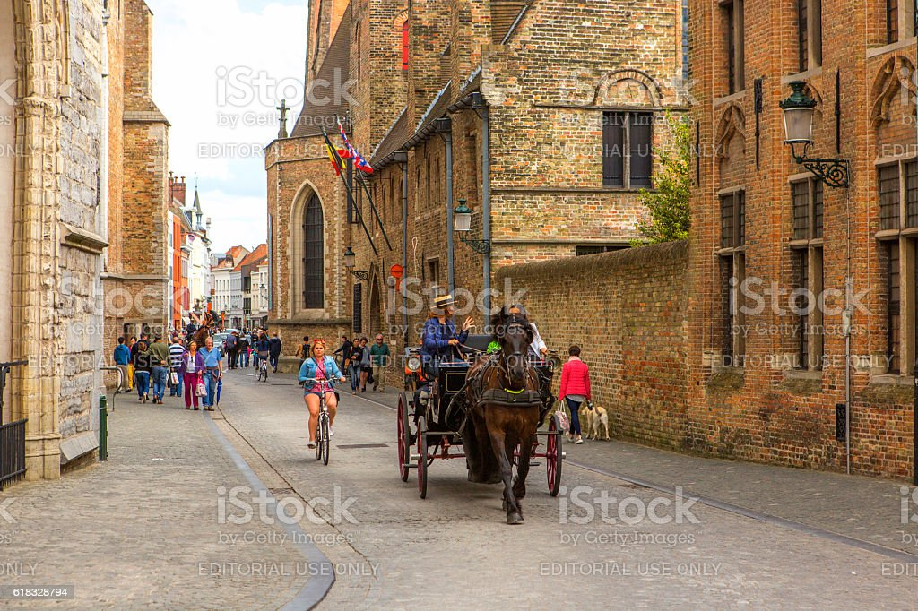People  at street with gothic old buildings at brugge belgium stock photo