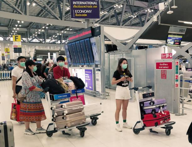 Menschen am Flughafen in Bangkok tragen Masken zum Schutz vor dem Coronavirus – Foto