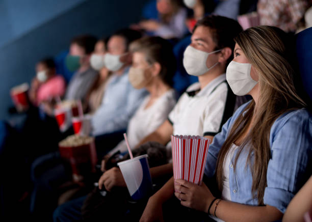 People at the cinema wearing facemasks while watching a movie stock photo