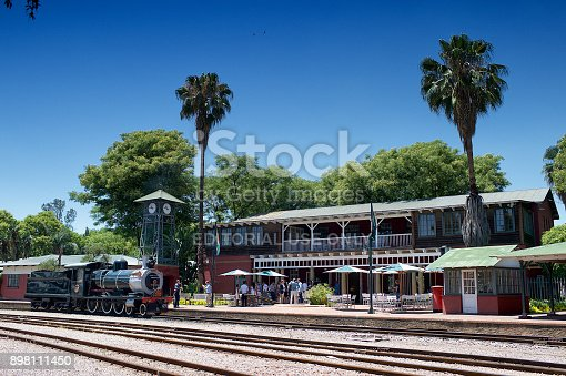 Rovos Rail Train, Pretoria Station, South Africa - 18 November, 2017 : People standing outside the Rovos Rail Pretoria Station waiting to board with the old train station and two palm trees with a clear blue sky.