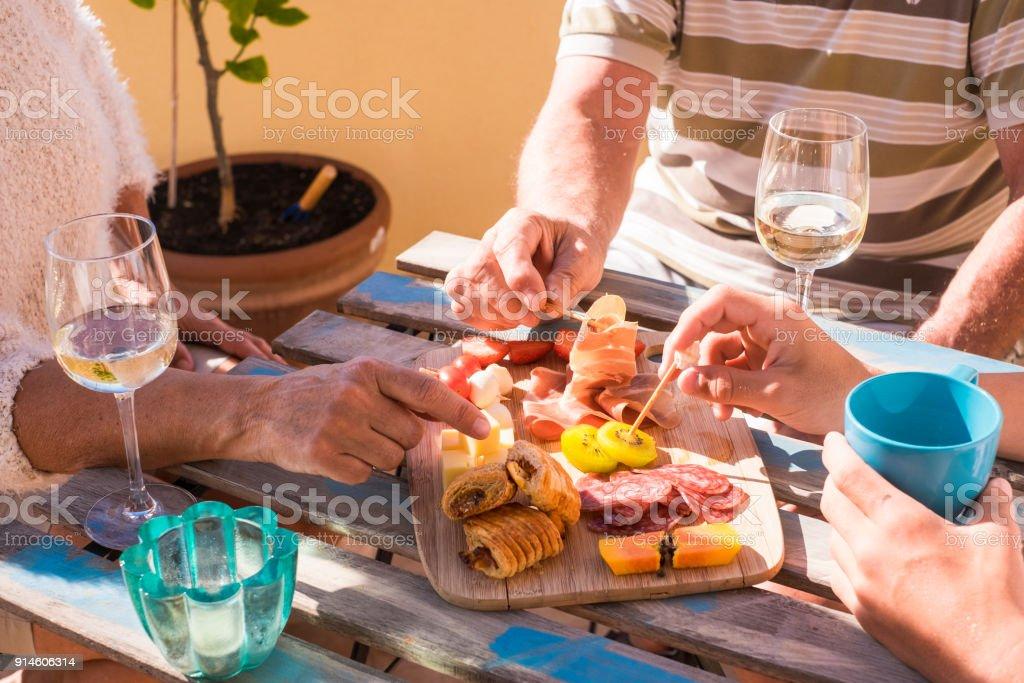 3 Personen am Tisch mit Essen und Wein – Foto
