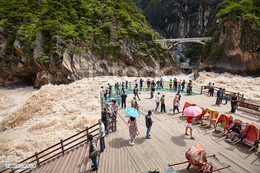 Jizha, China - September 24, 2017: People at the Tiger Leaping Gorge rough waters viewpoint. It is part of the Three Parallel Rivers of Yunnan Protected Areas World Heritage Site.