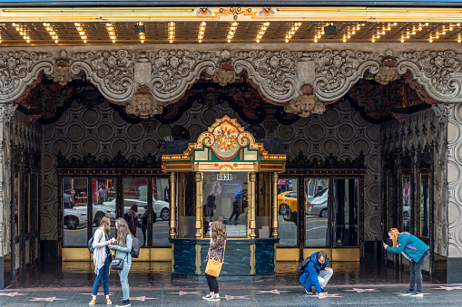 Los Angeles, USA - March 5, 2019: people at the walk of fame in Hollywood take pictures of the stars in front of historic cinema el Capitan.