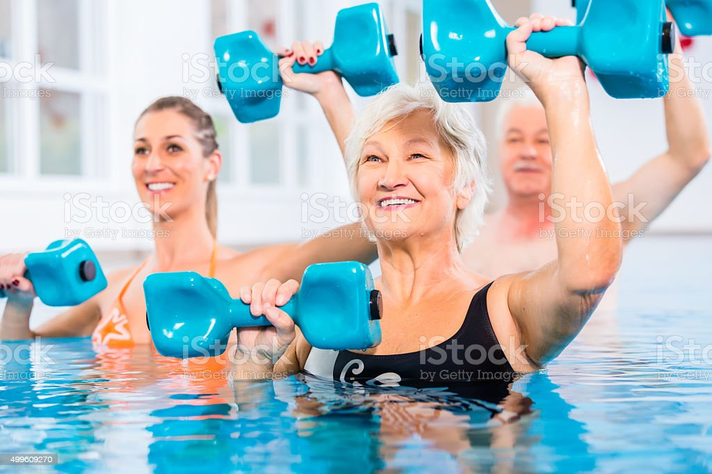 People young and senior in water gymnastics physiotherapy with...