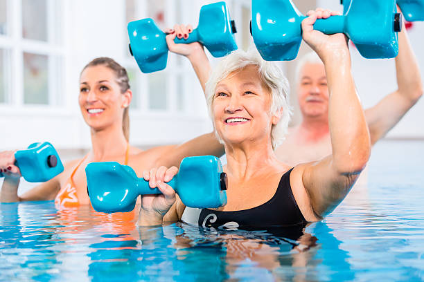 People at water gymnastics in physiotherapy People young and senior in water gymnastics physiotherapy with dumbbells alternative therapy stock pictures, royalty-free photos & images