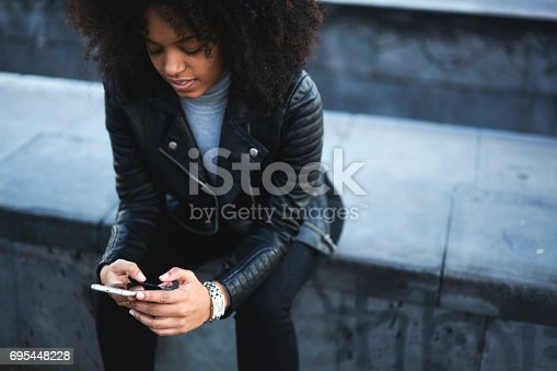 Attractive afro American girl spending time outdoors sitting on urban space background checking email waiting for confirmation from university