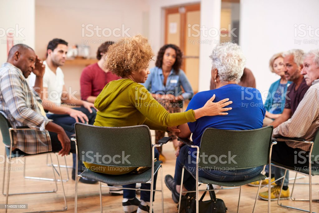 People Attending Self Help Therapy Group Meeting In Community Center