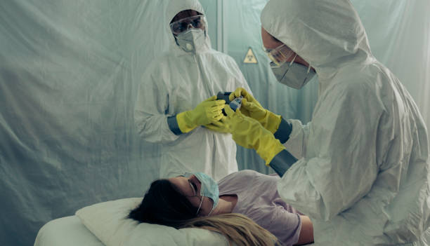 People attending to a woman with a virus lying on a stretcher Two people attending to a woman with a virus lying on a stretcher in a field hospital epidemic stock pictures, royalty-free photos & images