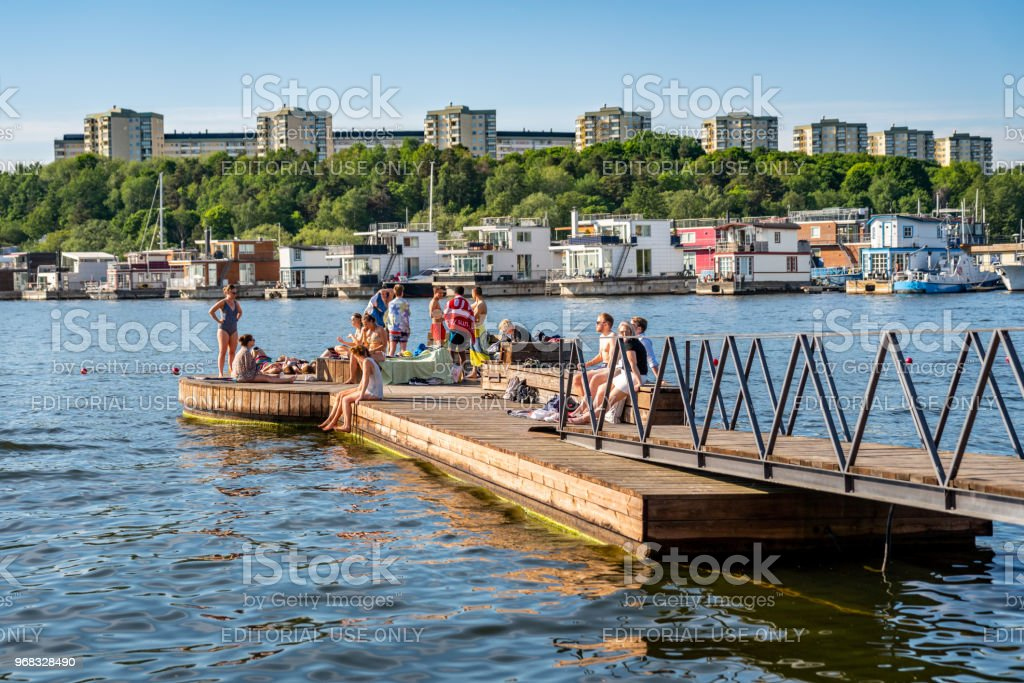 People bathing and relaxing on a boardwalk with buildings and house boats. stock photo