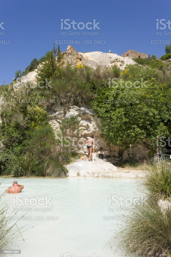 People bathing in the free area of Bagno Vignoni stock photo