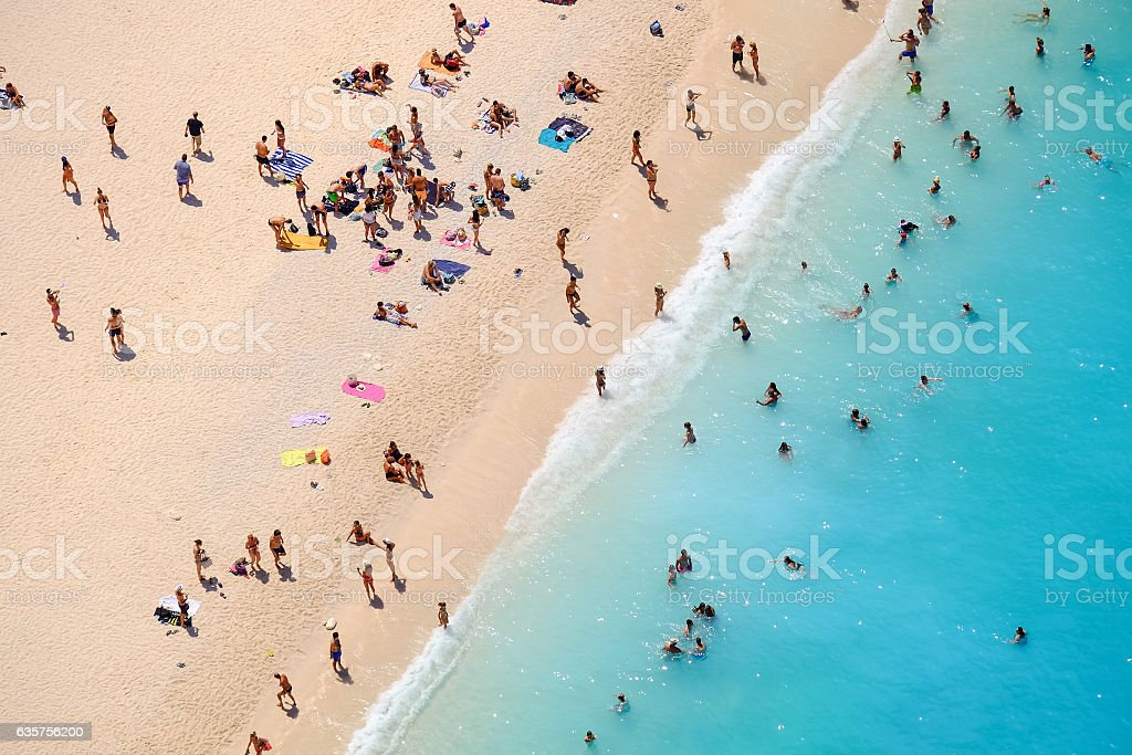 People bathing in the sun, swiming and playing games on stock photo
