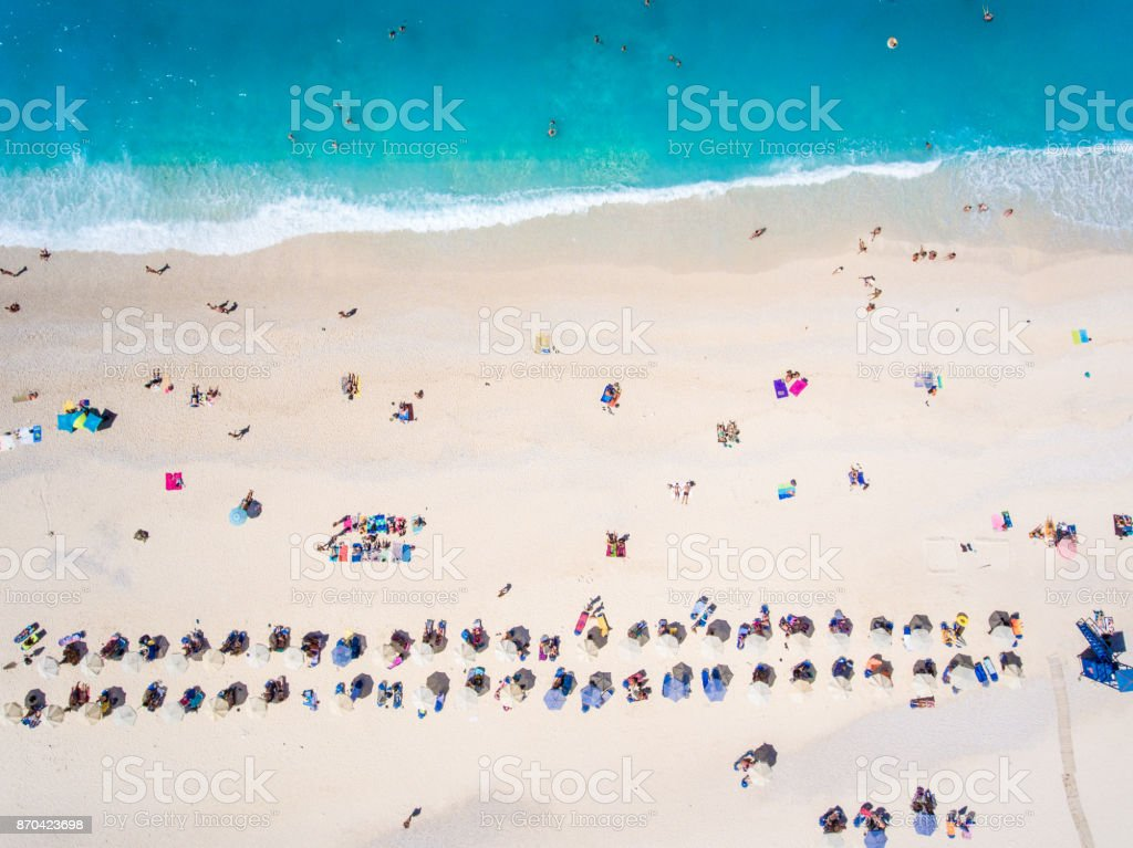 People bathing in the sun, swimming and playing games on the beach. Tourists on the sand beach in Kefalonia island, Greece stock photo