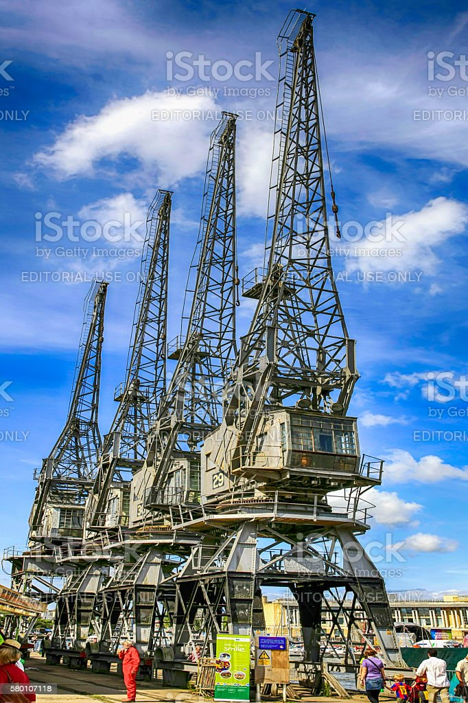People beneath the dockyard Cranes in Bristol harbor, UK stock photo