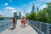 People bike and walk on the Schuylkill Banks Boardwalk in downtown Philadelphia, Pennsylvania, USA on a sunny summer day.