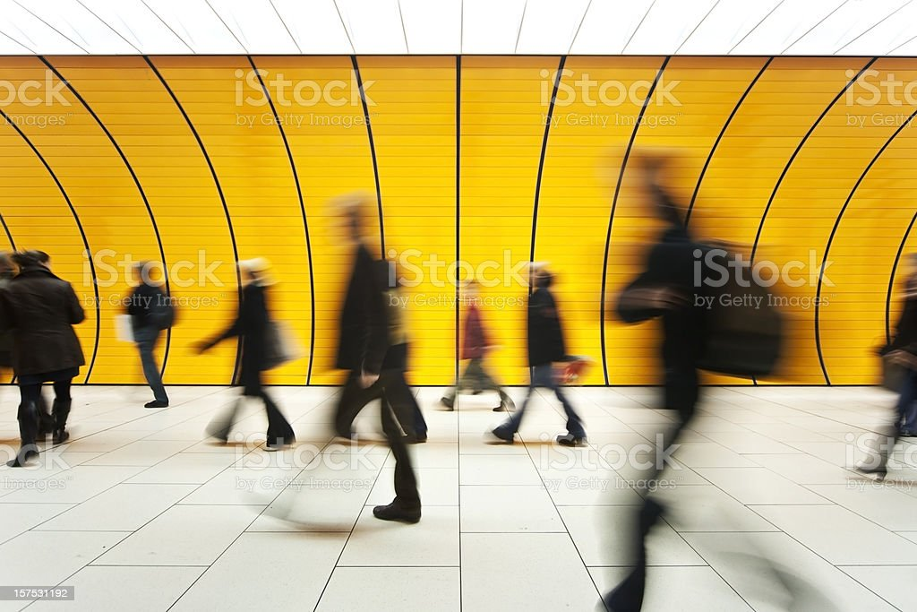People blurry in motion in yellow tunnel down hallway stock photo