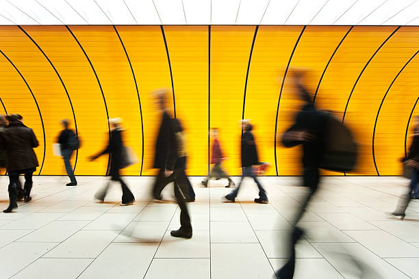 people blurry in motion in yellow tunnel down hallway - motion stock pictures, royalty-free photos & images