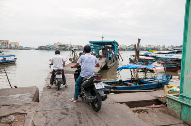 people boarding a ferry in my tho, vietnam - motorbike, umbrella stock photos and pictures