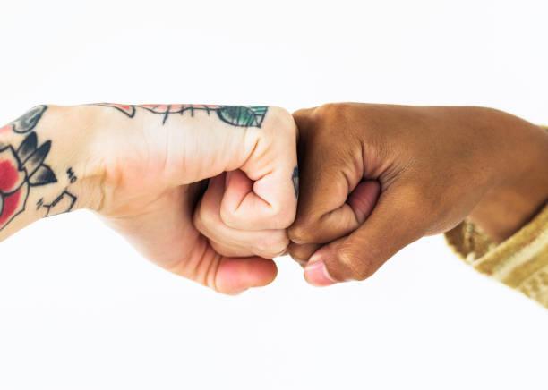 menschen, die ihre fäuste zusammen stoßen - freundin tattoos stock-fotos und bilder
