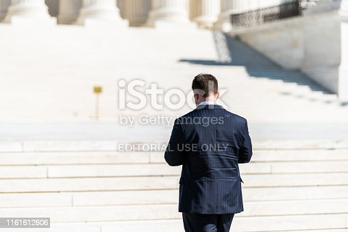 Washington DC, USA - October 12, 2018: People business man walking closeup back on steps of Supreme Court building marble stairs on Capital capitol hill with columns