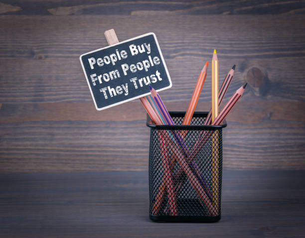 People Buy From People They Trust. A small blackboard chalk and colored pencil on wood background stock photo