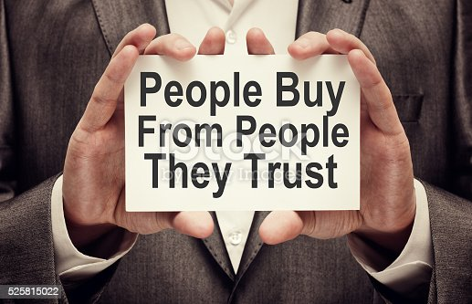 People Buy From People They Trust. Businessman holding a card with a message text written on it
