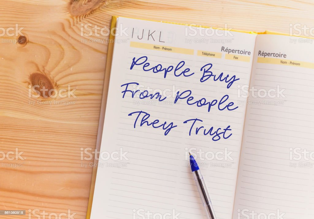 People Buy From People They Trust written on notebook stock photo