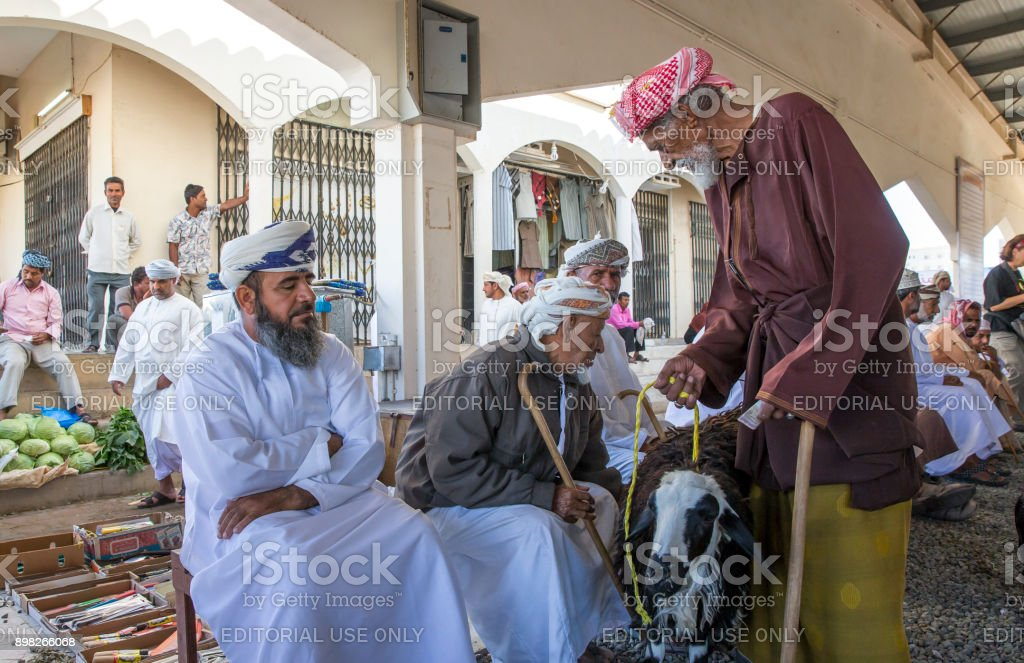 people buying and selling goats at a market stock photo