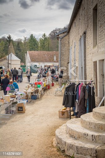People buying and selling Annual Rural brocante market (thrift 2nd hand boot sale) in Provenchères sur Marne, in the Haute Marne, France.