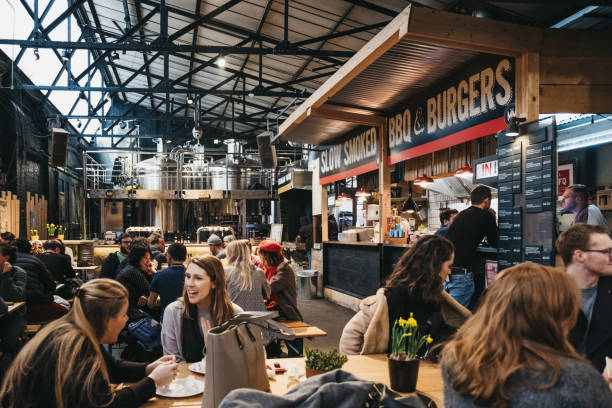 People by BBQ and burger stand in Mercato Metropolitano market in London, UK. London, UK - January 13, 2019: People by BBQ and burger stand in Mercato Metropolitano, the first sustainable community market in London focused on revitalising the area and protecting environment. mercato stock pictures, royalty-free photos & images