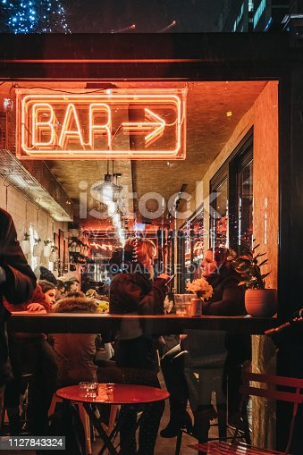 istock People by illuminated window and neon sign on Bar in Canary Wharf, London, UK. 1127843324