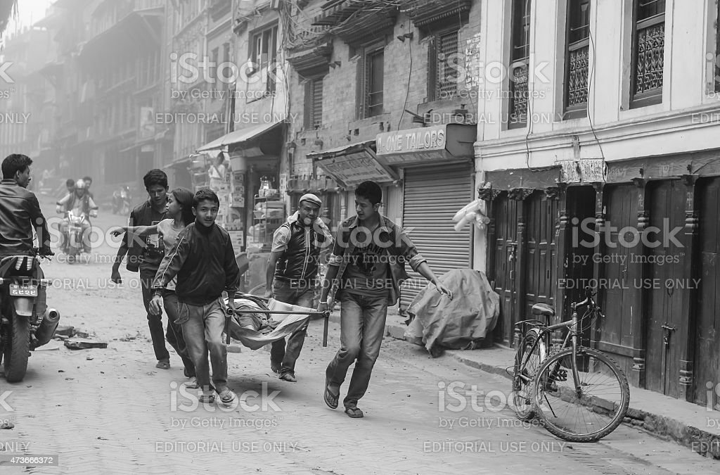 people carry stretcher to hospital after earthquake in nepal stock photo