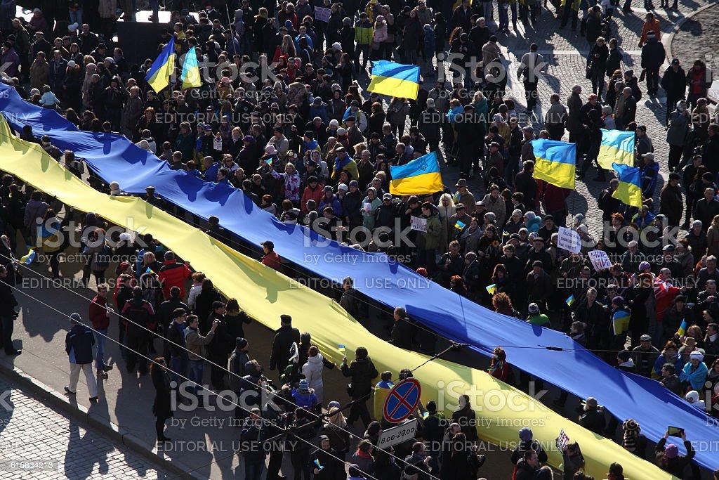 People carrying long national flag of Ukraine stock photo