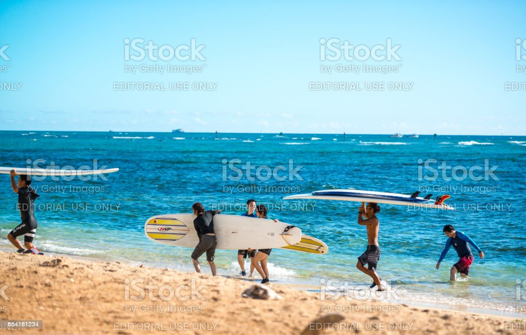 People carrying paddle boards from the water to the beach, Honolulu, Hawaii, USA stock photo