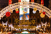 Color image depicting crowds of people on the street at one of the many Christmas markets in Vienna, Austria. The illuminated lights of the Christmas market can be seen beyond.