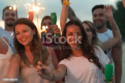 istock People celebrating the new year on the beach with sparkler 1089406044