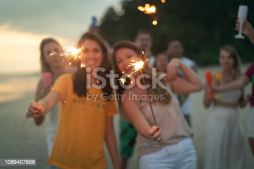 istock People celebrating the new year on the beach with sparkler 1089407658